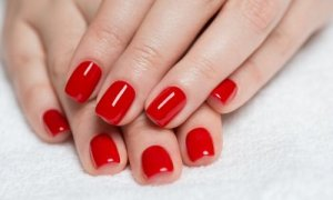 Fingernails with red nail polish.